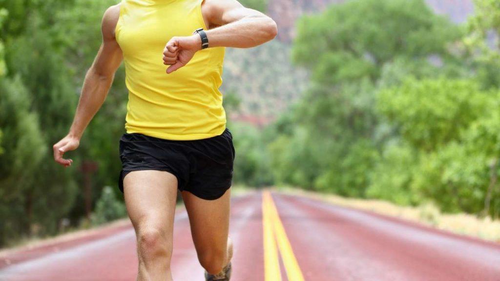 רץ במסלול ריצה מסתכל על השעון בזמן ריצה